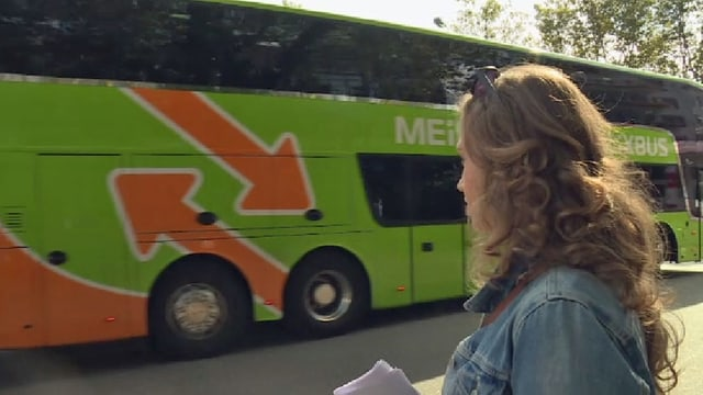 Eine Frau schaut einem Reisebus nach.