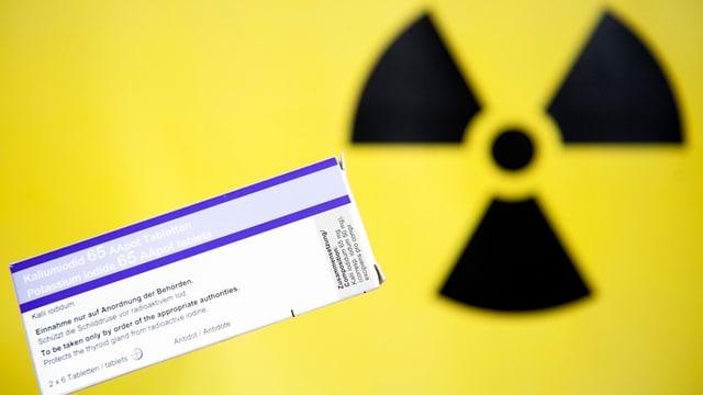 Schwarzes Strahlen-Symbol auf gelbem Grund mit einer Packung Joftabletten