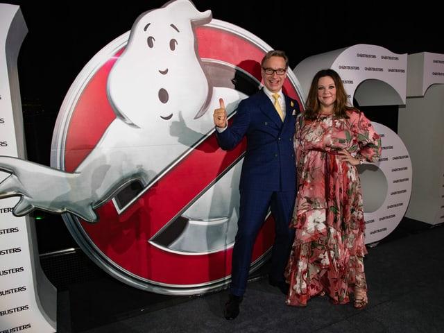 Melissa McCarthy und Paul Feig stehen vor einem Ghost Busters Schild.