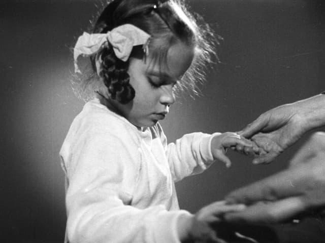 Ein Mädchen mit geschlossenen Augen hält die Hände einer erwachsenen Person.