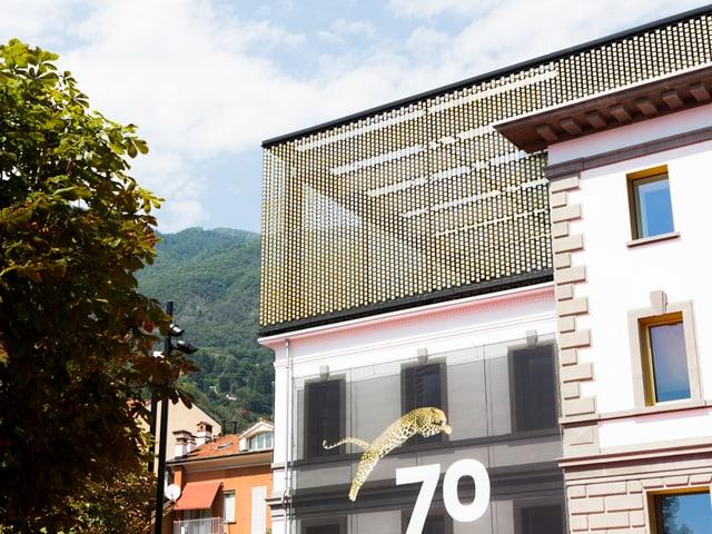 Teil eines grossen Gebäudes. Auf dem Dach ein halbtransparenter Aufbau mit goldenen Elementen. Am Gebäude hängt eine Fanhe mit einem springenden Leoparden und der Zahl 70.