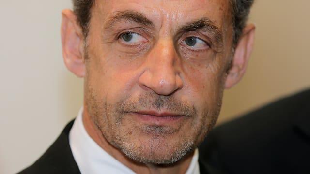 Ernstes Gesicht von Nicolas Sarkozy mit Bartstoppeln.