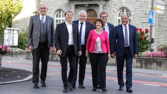 Fünf Männer in Anzug und eine Frau in pinkem Jäckchen.