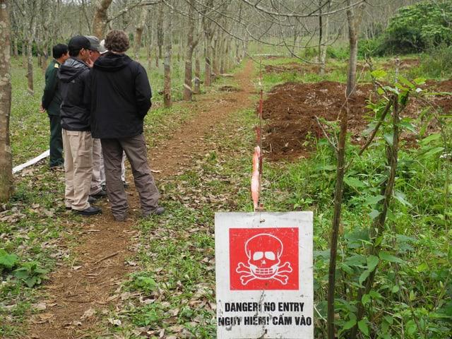 Männer stehen neben einem Feld, vor dem ein Schild steht, u.a. mit der engl. Aufschrift: Danger! No entry