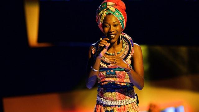 Eine Sängerin in afrikanischer, mit bunten Mustern geschmückter Tracht hält ein Mikrofon in der Hand.