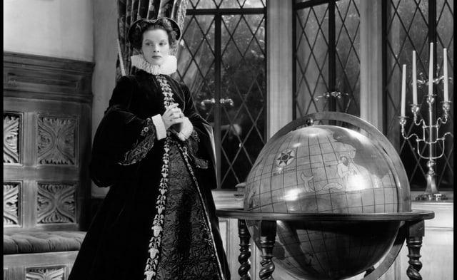 Eine Frau in edlem Gewand steht vor einer riesigen Weltkugel und schaut nachdenklich zur Seite.