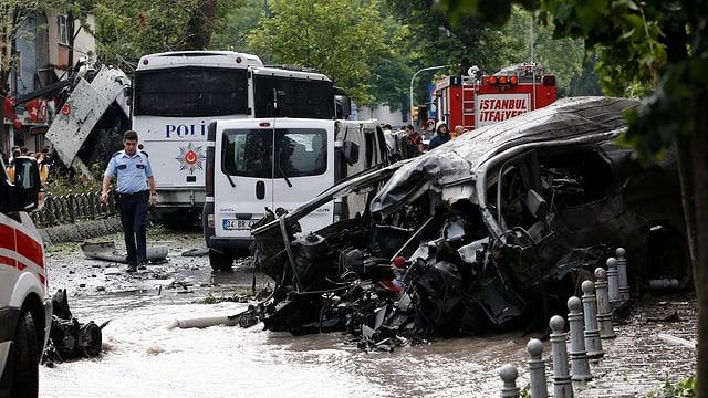 Autowrack und Polizeifahrzeuge am Ort der Explosion