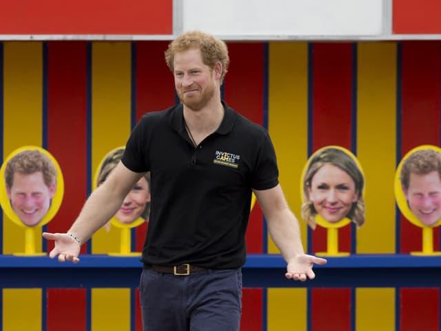 Prinz Harry vor Aufstellern, auf denen ein Foto seines Kopfes drauf ist.