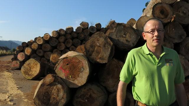 Ein Mann steht vor aufgeschichteten Holzstämmen.