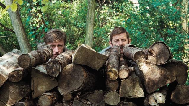 Zwei Männer spähen hinter aufgebahrtem Holz hervor.