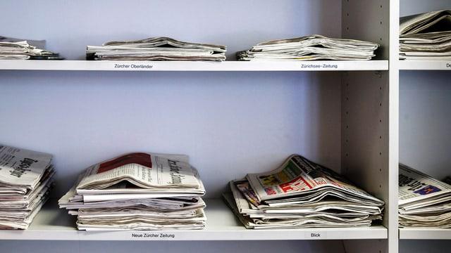 Zeitungen liegen in Regal.