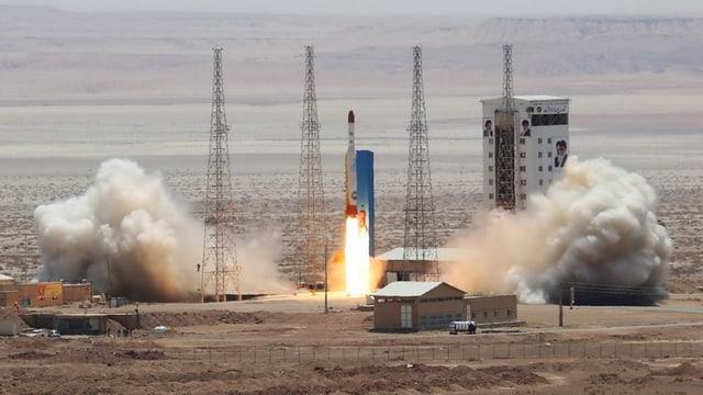Raketenstart in einer Wüstenlandschaft, rechts ein Gebäude mit Bildern Ayatollah Chemeinis