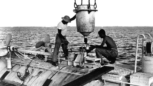 Vor ihrem Rekordtauchgang in den Marianengrabgen laden Ernest Virgil und Jacques Piccard das Tiefsee-Tauchgerät mit Stahl.