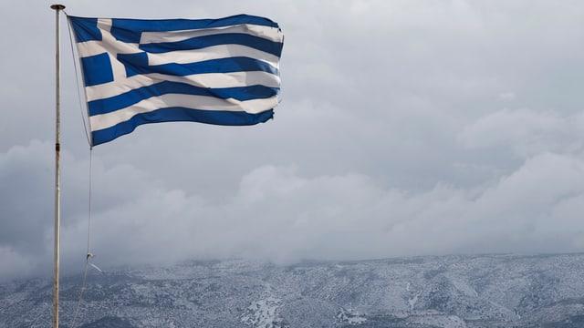 Eine griechische Flagge weht im Wind. Im Hingergrund Himmel und eine Bergkette.