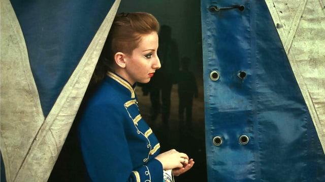 Eine Frau steht vor dem Eingang zu einem Zirkuszelt.