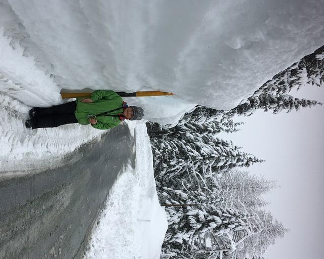 Bub steht auf eienr Strasse neben einer zwei meter hohen Schneewand.