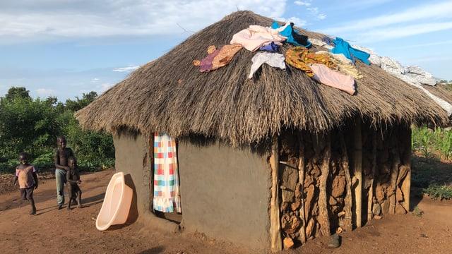 Hütte mit Strohdach, Kleider darauf, neben Hütte Mann mit Kindern.