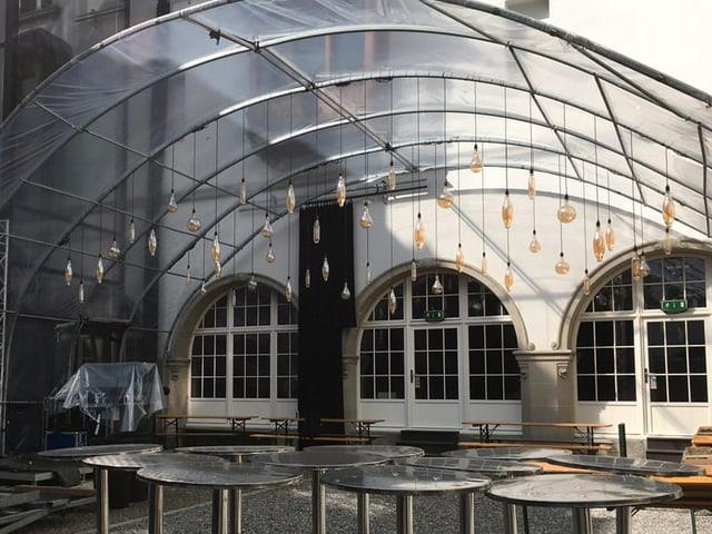 Plexiglasdach mit Hängelampen in einem Innenhof