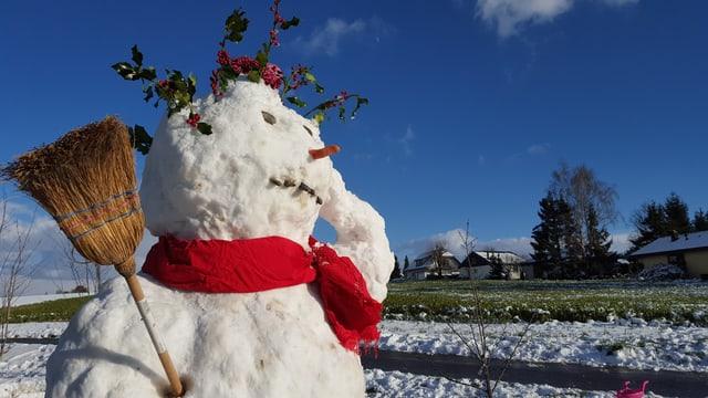 Ein Schneemann schmilzt langsam dahin. Die Sonne scheint vom blauem Himmel.