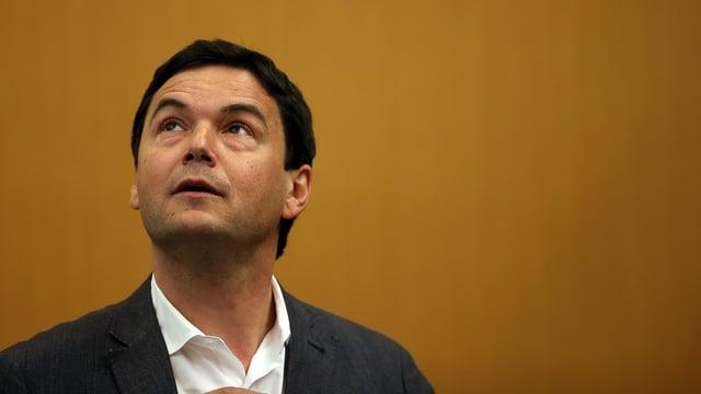 Thomas Piketty schaut nach oben. Er trägt einen Anzug.