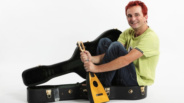 Christian Schenke mit roten Haaren sitzt in einem Gitarrenkoffer und hällt eine Ukulele.