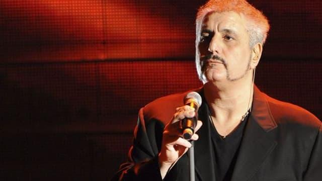 Der Sänger Pino Danile auf einer rot belichteten Bühne.