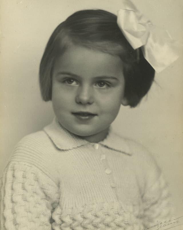 Schwarz-Weiss-Fotografie von einem kleinen Mädchen, das eine grosse weisse Schleife in den Haaren trägt.
