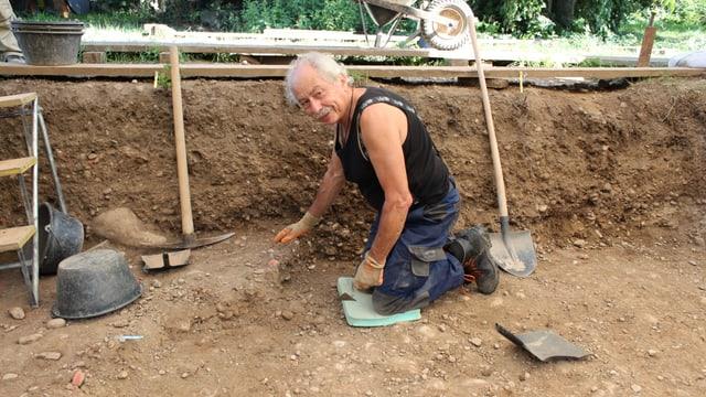 Mann kniet in Grube
