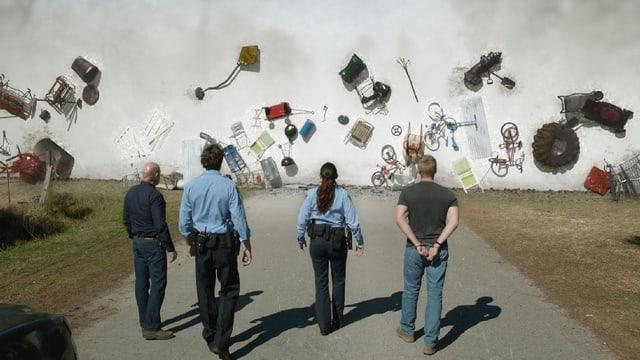 Vier Menschen stehen auf einer Strasse, vor ihnen fliegen verschiedenste Gegenstände durch die Luft.