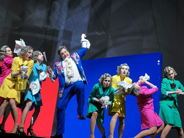 Sieben Frauen in pastellfarbenen Kostüm auf einer Theaterbühne.