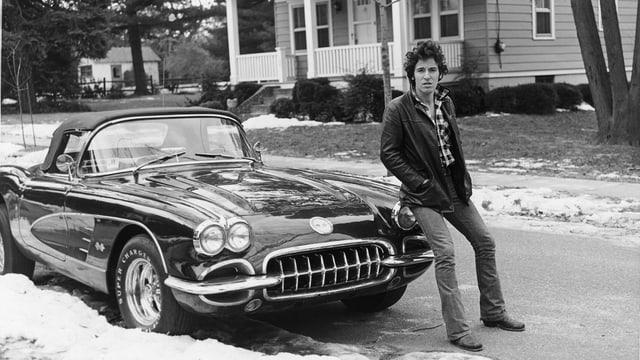 Auf einer Strasse in Amerika: der junge Bruce Springsteen sitzt auf der Haube seiner Corvette.