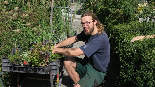 Fabian Zurflüh putzt die Pflanzen für den Verkauf heraus.