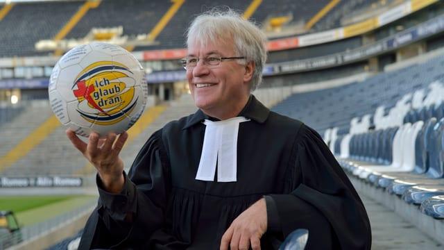 Pfarrer Eckert im Stadion von Eintracht mit einem Ball in der Hand.