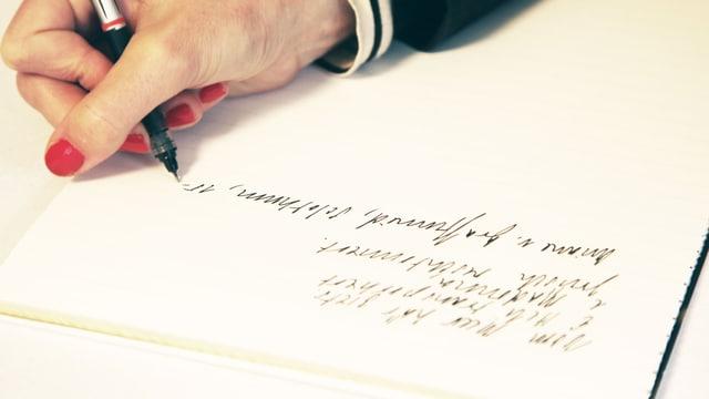 Frauenhand mit roten Fingernägeln beim Schreiben