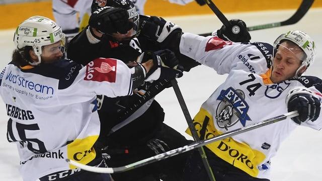 Zwei Spieler des EV Zug nehmen einen Spieler von Lugano in die Mangel.