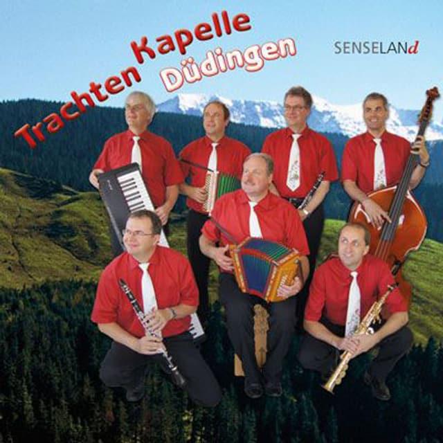 Rote Hemden und weisse Krawatten. Die Band sitzt vor Bergkulisse.