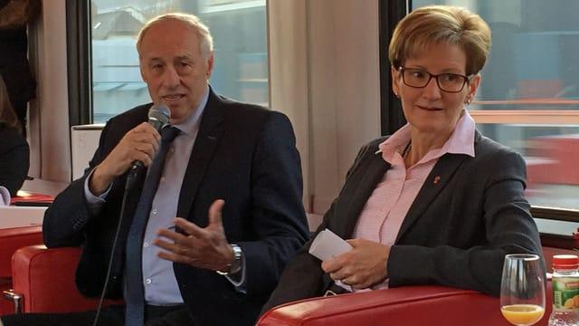 Jean-Marie Zoelle und Sabine Pegoraro sitzen im Zug. Er hält ein Mikrophon in der Hand und sagt etwas.
