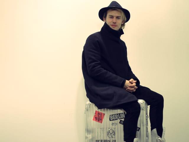 Tobias Jundt sitzend auf Reisekoffer