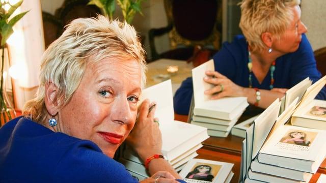 Eine Frau mit kurzen Haaren sitzt an einem Tisch voller Bücher.