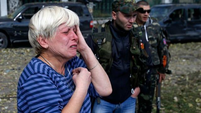 Eine weisshaarige Frau weint und greift sich mit einer Hand an den Kopf; im Hintergund zwei bewaffnete Männer.