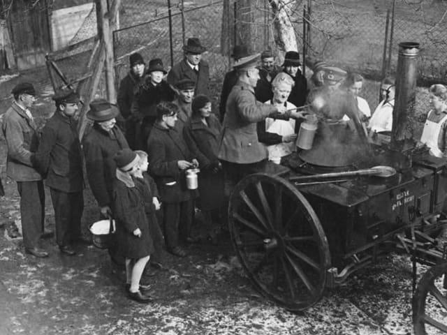 Ein paar Menschen bekommen Essen von der Reichswehr.