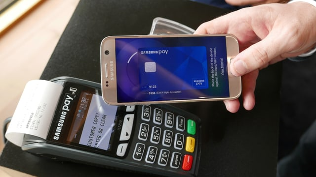 Eine Hand hält ein Smartphone mit Samsung Pay an einen Kreditkartenleser.