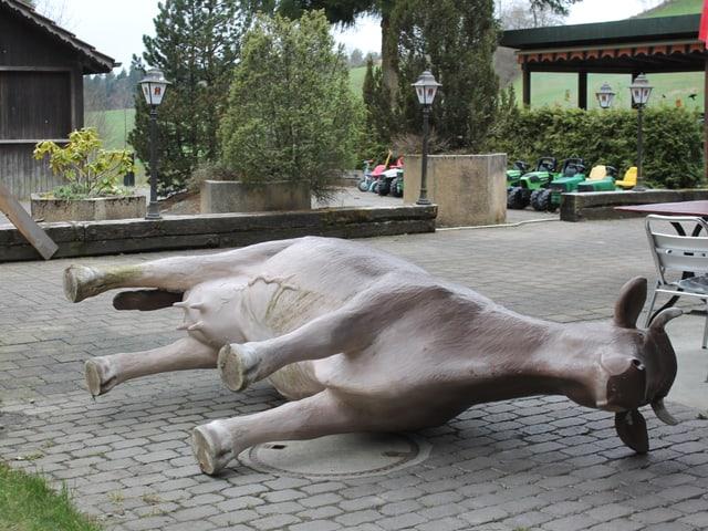 Ein Kuh aus Kunststoff liegt auf dem Boden.