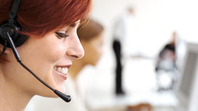 Eine lächelnde Frau mit Headset.