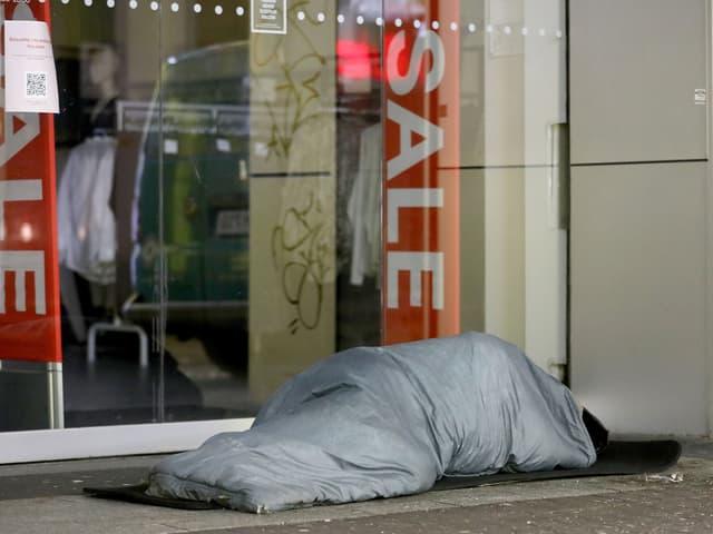 Obdachloser schläft vor Ladenlokal