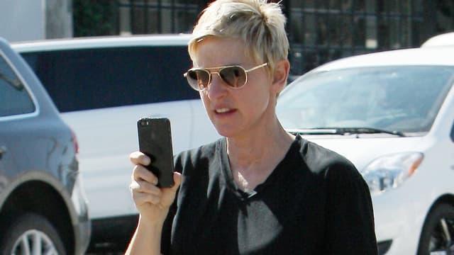 Ellen DeGeneres mit Sonnenbrille und einem schwarzen «iPhone» in der Hand.