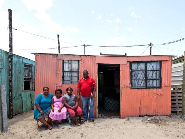 Familie vor rosa Blechhütte.