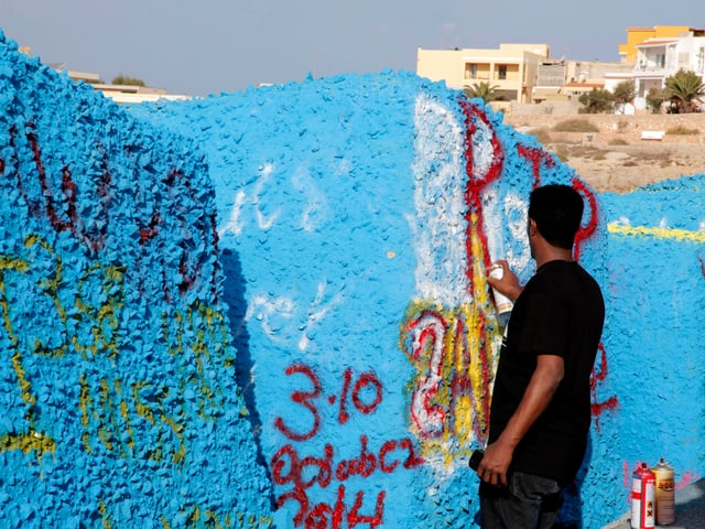 Man schreibt auf blau eingefärbten quadratischen Felswürfel.