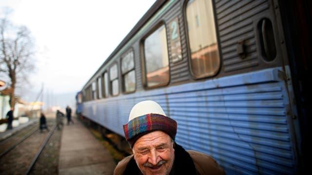 Ein lächelnder, älterer Mann vor steht an einem Bahnhof neben einem Zug.