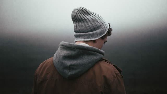Junger Mann mit Kapuzenjacke und Mütze steht mit dem Rücken zur Kamera und schaut zu Boden.